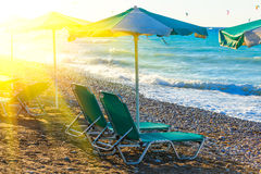Beach chairs and umbrella on the shore of a pebbly beach Greece Rhodes with sun flare twilight time royalty free stock images