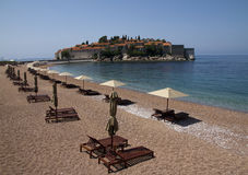 Beach chairs and umbrellaa. Beach chairs and umbrellas on a beautiful beach with view on the Sveti Stefan Island stock photo