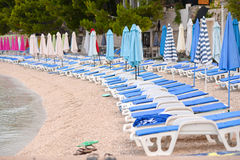 Beach chairs and umbrellas on the beach prepared. Royalty Free Stock Image