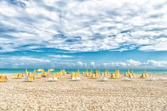 Beach chairs and umbrellas on cloudy sky in miami, usa. Sea beach with white sand and blue water on sunny day. Summer vacation on Royalty Free Stock Images