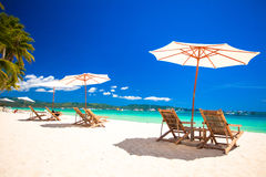 Beach chairs and umbrellas on exotic tropical. Beach chairs on exotic tropical white sandy beach Royalty Free Stock Photos