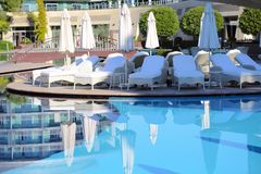 Beach chairs and umbrellas about pool. Stock Photos