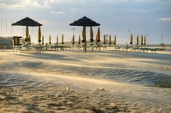 Beach chairs and umbrellas. Rimini Beach just before sunset, Emilia Romagna, Italy royalty free stock image