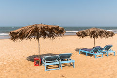 Beach chairs and umbrellas Stock Images