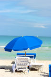 Beach chairs under blue umbrella on the ocean beach. Royalty Free Stock Photos