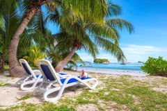 Beach chairs under a palm tree on tropical beach at Seychelles. Stock Photography