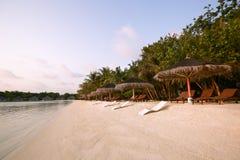 Beach chairs under straw umbrellas. Indian ocean coastline on Maldives island. White sandy beach and calm sea. Travel. Beach chairs under umbrellas. Indian ocean stock images