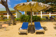 Beach chairs under a thatched roof in the tropics Stock Photos