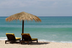 Beach chairs under an umbrella next to the sea Stock Photography