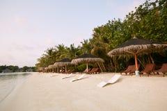 Beach chairs under straw umbrellas. Indian ocean coastline on Maldives island. White sandy beach and calm sea. Travel. Beach chairs under umbrellas. Indian ocean stock photos