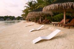 Beach chairs under straw umbrellas. Indian ocean coastline on Maldives island. White sandy beach and calm sea. Travel. Beach chairs under umbrellas. Indian ocean royalty free stock image