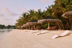 Beach chairs under straw umbrellas. Indian ocean coastline on Maldives island. White sandy beach and calm sea. Travel. Beach chairs under umbrellas. Indian ocean royalty free stock images