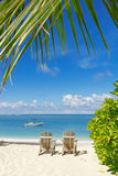 Beach chairs on white sand. With blue sky backgrounf and palm leafs on foreground royalty free stock photos