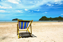 Beach chairs on the white sand beach with cloudy blue sky Royalty Free Stock Photos