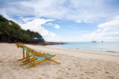 Beach chairs on the white sand beach with cloudy blue sky Royalty Free Stock Photography