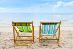 Beach chairs on the white sand beach with cloudy blue sky Royalty Free Stock Image