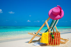 Beach chairs on the white sand beach with cloudy blue sky and sun Royalty Free Stock Image
