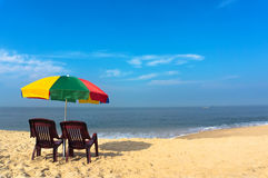 Beach chairs on the white sand beach with cloudy blue sky and sun. Two chairs under an umbrella at the Marai beach in Kerala India Royalty Free Stock Image