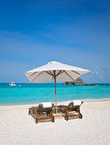 Beach chairs with white umbrella at ocean front Stock Images