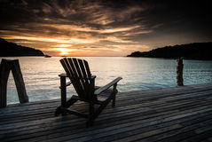 Beach chairs on a wooden bridge Stock Photo