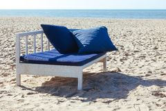 Beach chaise lounge sea sand sky horizon signs advertising black blue cushions ocean bench. Beautiful beach with two blue cushions on the chaise lounges. The sea royalty free stock image