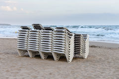Beach chaise lounges stacked in a row on the beach. Image of beach chaise lounges stacked in a row on the beach stock photo