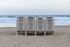 Beach chaise lounges stacked in a row on the beach. Image of beach chaise lounges stacked in a row on the beach stock images