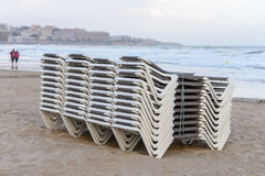 Beach chaise lounges stacked in a row on the beach. Image of beach chaise lounges stacked in a row on the beach stock photos