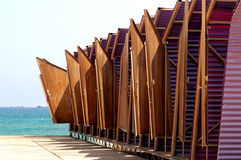 Beach changing huts. A view of a row of small, wooden changing huts next to the water at a popular beach Royalty Free Stock Image