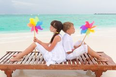 Beach children with pinwheels. Two children sitting back-to-back on a wooden platform on a beach, holding colorful pinwheels Stock Photography