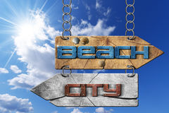 Beach and City - Directional Signs. Wooden directional sign with two arrows in opposite direction hanging with metal chain, with text beach and city on blue sky Stock Images