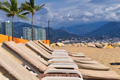 Beach, city and ocean view in Puerto Vallarta Mexico with beach chairs and coastline. Beach, city and ocean view in Puerto Vallarta Mexico with beach chairs and Stock Photo