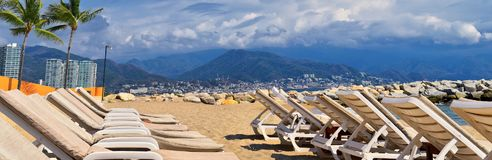Beach, city and ocean view in Puerto Vallarta Mexico with beach chairs and coastline. Beach, city and ocean view in Puerto Vallarta Mexico with beach chairs and Royalty Free Stock Photo