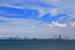 The beach with the city at Pattaya, Thailand. The beach with the city and the blue sky and the clouds at Pattaya, Thailand Stock Photo