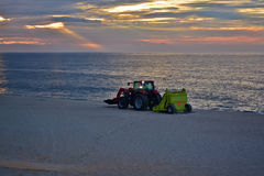 Beach Clean Up Beneath the Sunrise. A man operates heavy machinery, cleaning up the empty beaches at sunrise Stock Photo