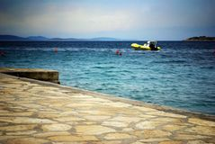 Beach and clear sea with cloudy sky and motorboat, Croatia Dalmatia Stock Photo