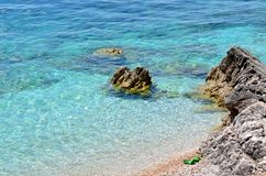 Beach with clear water and green slippers Royalty Free Stock Photo