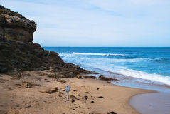 Beach and the cliff. Warning signs on the beach, caution sings on the beach. Sand rocks cliff. Beautiful blue ocean. Waves washing off the beach sand. Barwon Stock Images