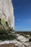 Beach cliffs scenic views. A stunning view across an English Channel beach in Sussex with high white cliffs and blue sky and seaweed stains on the high water Royalty Free Stock Photos