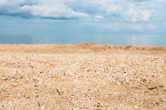 Beach close up and white clouds over blue sea. Foreground focus - sand and shelly beach close up and white clouds over blue sea. Coasline of Sea of Azov, Temryuk Royalty Free Stock Photos