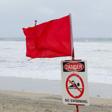 Beach closed. Tattered red flag flying in the wind and warning sign saying danger, no swimming, beach closed, on a stormy day at the beach with big waves royalty free stock image