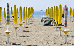 Beach with closed sun umbrellas Stock Photography