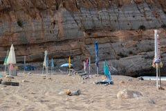 Beach with closed umbrellas. Empty sandy beach near rock with closed umbrellas in El Portus; Spain Stock Image