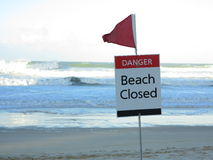 Beach closed warning sign by dangerour conditions. The Red Flag - an Australian warning sign for beach closure - with the rough sea in the background by a strong Royalty Free Stock Photo