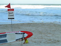 Beach closed sign and lifeguard surfboard Royalty Free Stock Photos
