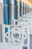 Beach closets with famous names in Deauville, France. FRANCE, DEAUVILLE - SEPTEMBER 27: original beach closets with famous names on promenade Des Planches in stock photos