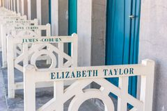 Beach closets with famous names in Deauville, France. FRANCE, DEAUVILLE - SEPTEMBER 27: original beach closets with famous names on promenade Des Planches in royalty free stock photo