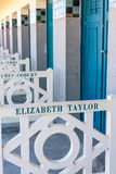 Beach closets with famous names in Deauville, France. FRANCE, DEAUVILLE - SEPTEMBER 27: original beach closets with famous names on promenade Des Planches in stock image