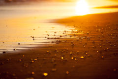 Beach closeup in the rays of the setting sun. With small pebbles and the reflection in the water. Black sand, Bali Indonesia Royalty Free Stock Photos