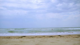 Beach on a cloudy day. Waves washing over the sand. 23. 976p video. Long shot stock video footage